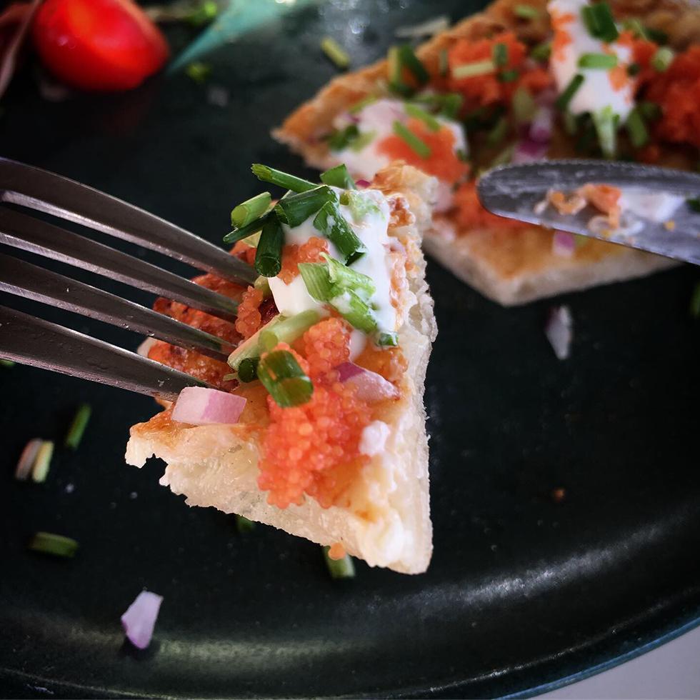 Parmesanpizza toppad med rom, rödlök och creme fraiche